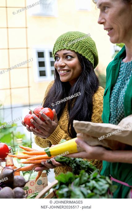 Young women buying home-grown vegetables