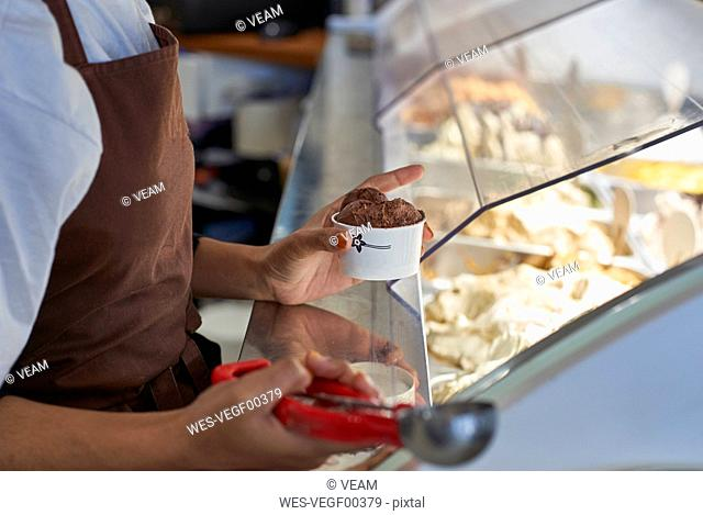 Young woman working in ice cream parlour, filling cup with icecream