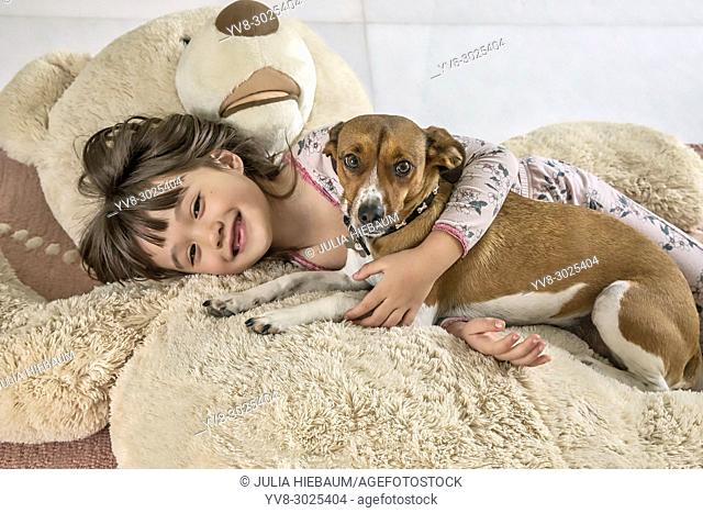 Six year old girl and her doggie laying on a giant bear