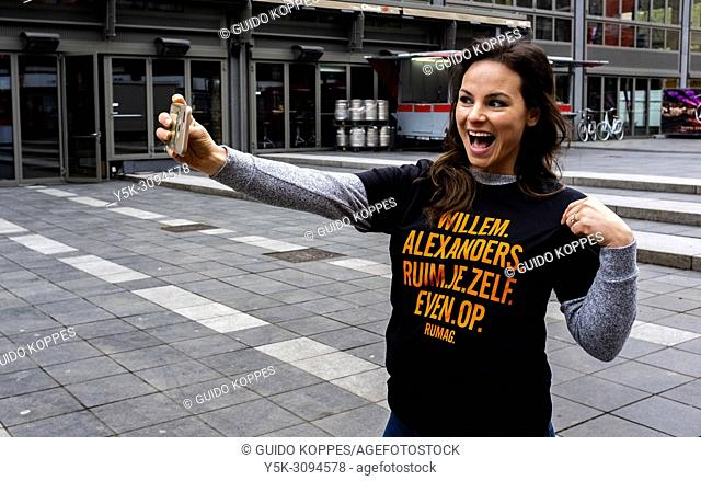 Rotterdam, Netherlands. Young adult brunette woman, making a selfie in a new t-shirts at Kingsday 2018. Making over enthusiastic selfies has become a fashion...