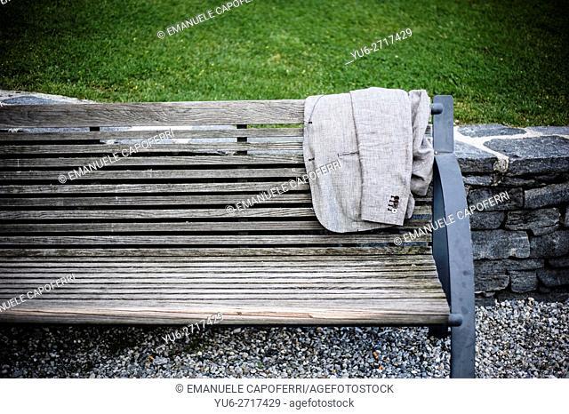 Elegant mens jacket resting on the bench in a park