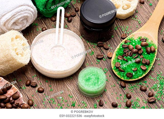 Anti-cellulite cosmetics with caffeine. Wooden spoon with green coarse sea salt and coffee beans, natural body scrubs, skin care cream, body scrubbers, towels