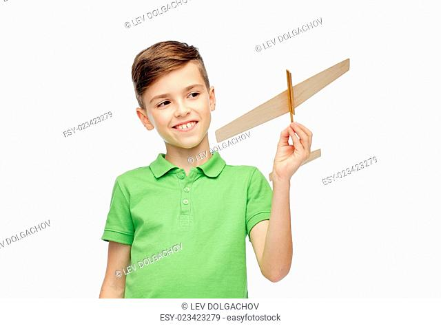 childhood, dream and people concept - happy smiling boy in green polo t-shirt with toy airplane