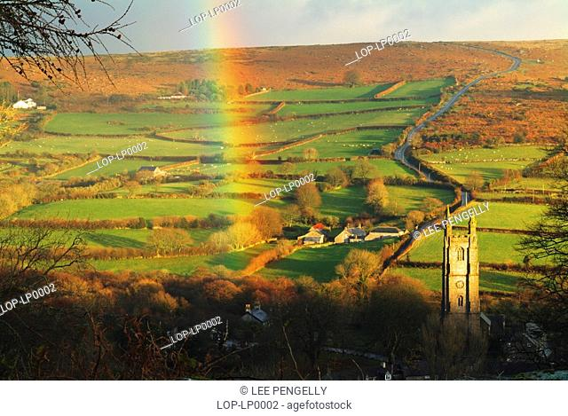 England, Devon, Widecombe in the Moor, A colourful autumnal rainbow over the village of Widecombe in the Moor