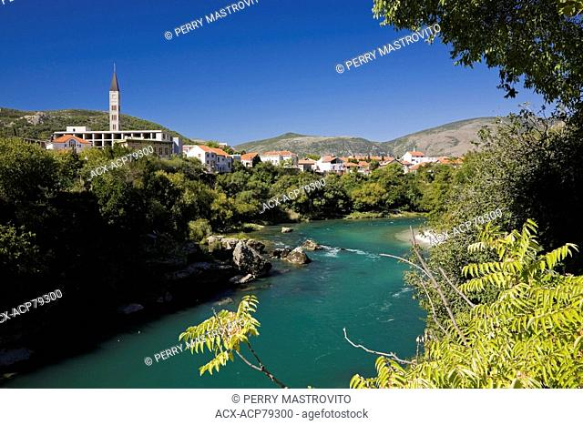 Neretva river with the bell tower of the St. Peter & St. Paul church and residential homes, Mostar, Bosnia and Herzegovina, Eastern Europe