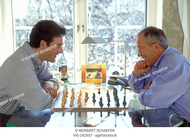 indoor, profile, 2 men sit at a glasstable in front of the window playing chess  - GERMANY, 11/03/2005