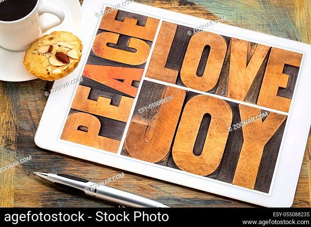 love, joy and peace word abstract on a digital tablet with a cup of coffee