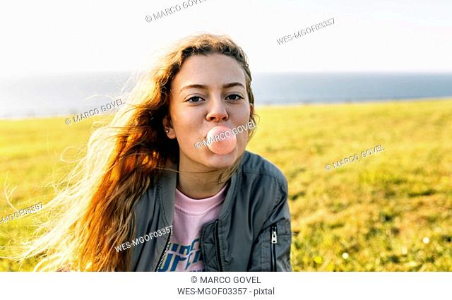 Teenage girl making a gum bubble outdoors