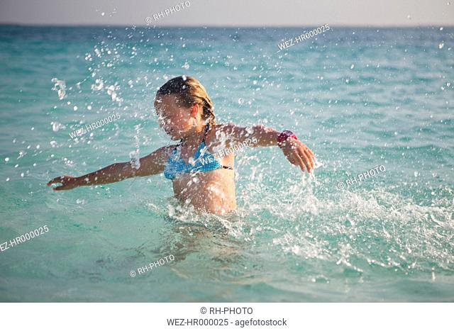 Tanzania, Zanzibar Island, girl spashing in the sea