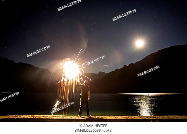Caucasian man holding sparkler on waterfront at night