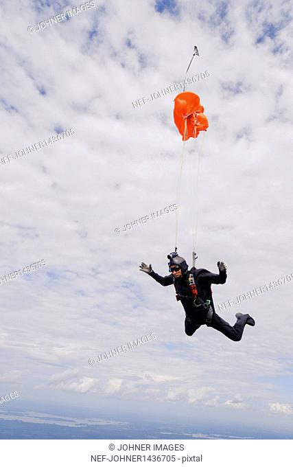 Skydiver with chute opening mid-air