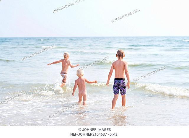 Three boys walking in sea on beach
