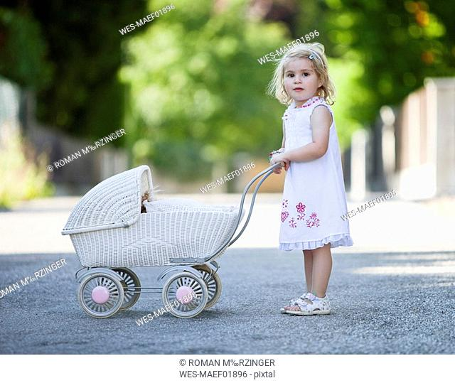 Germany, Bavaria, Girl 2-3 playing with toy baby carriage