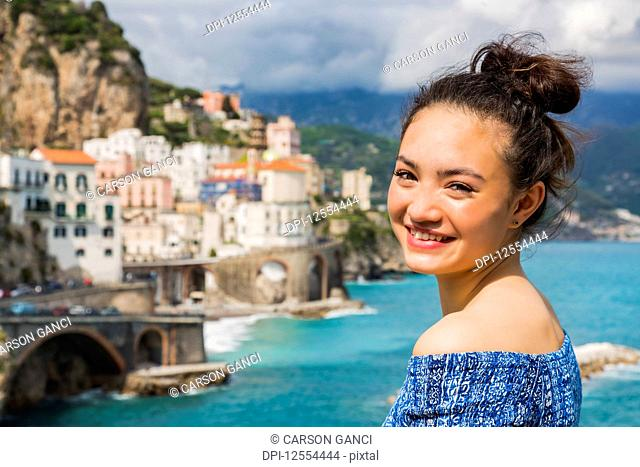 A young woman poses with the view of the Amalfi coastline and the Mediterranean Sea in the background; Amalfi, Italy