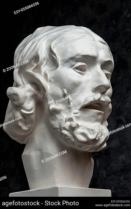 White gypsum copy of ancient statue of John the Baptist head for artists on a dark textured background. Plaster sculpture man face