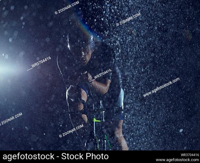 triathlon athlete riding professional racing bike at night with bad weather and falling rain