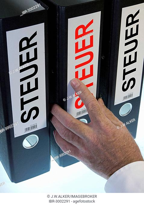 Hand reaching for file folders labeled Steuer, German for tax