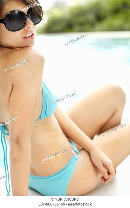 Young sexy female in bikini and sunglasses sitting by the swimming pool