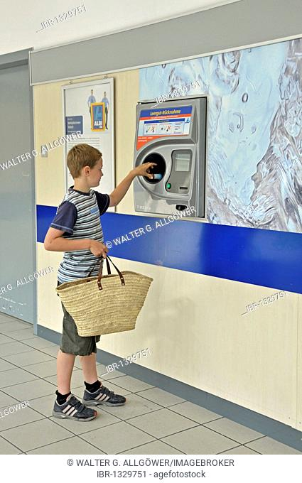 Boy, 9, returning empty deposit bottles in an automatic machine at an ALDI discounter store, Cologne, North Rhine-Westphalia, Germany, Europe