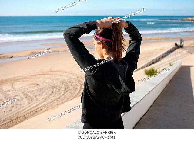 Rear view of young woman at beach tying hair in ponytail, Carcavelos, Lisboa, Portugal, Europe