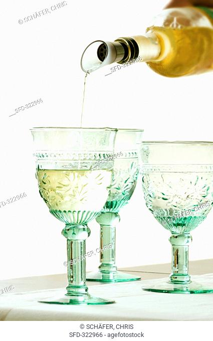 White Wine Pouring from Bottle into Glass, White Background