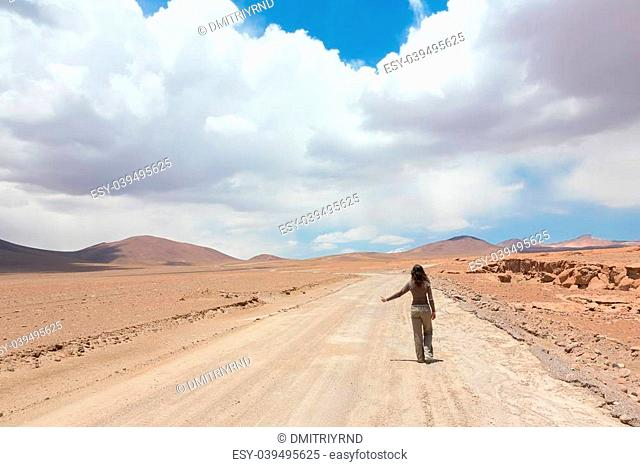 Woman hitchhiking the car on deserted road in Bolivia