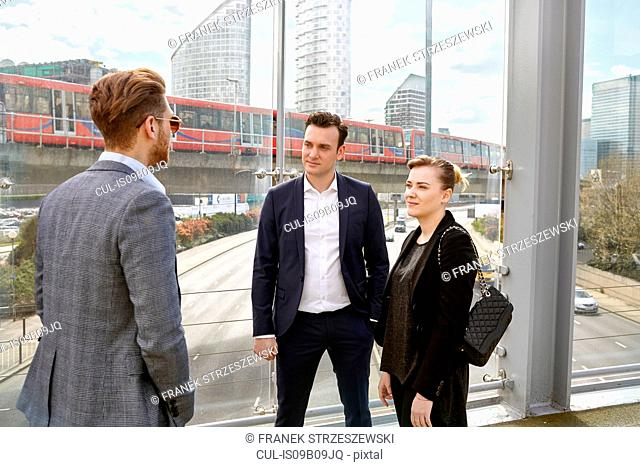 Businessmen and woman having discussion on footbridge, London, UK