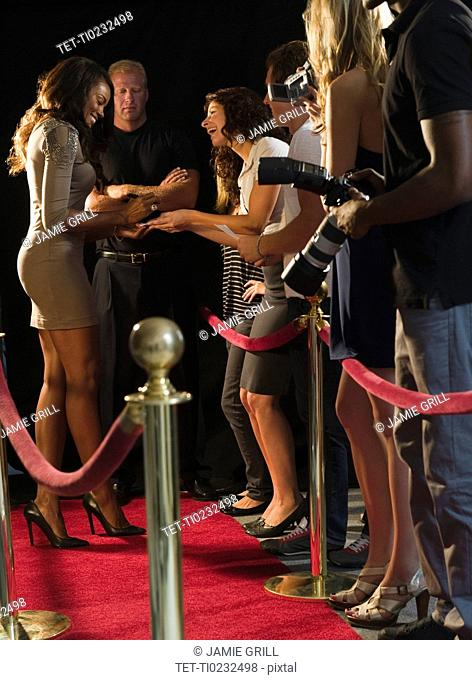 Celebrities signing autographs at red carpet event