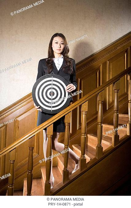 a business woman in suit with a target in her hands