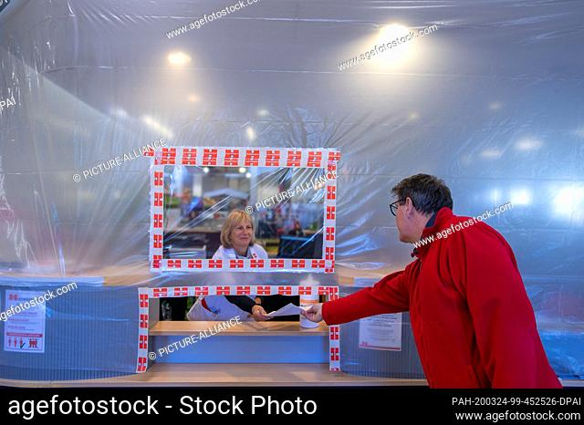 24 March 2020, Mecklenburg-Western Pomerania, Schwerin: An employee gives an invoice to a customer at the cash desk area in the trading yard behind a temporary...