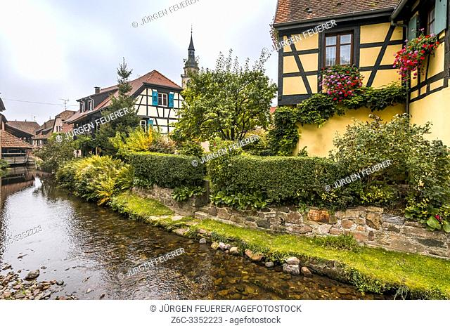 old village Andlau, Alsace Wine Route, France, half-timbered houses and flower decoration at the brook side