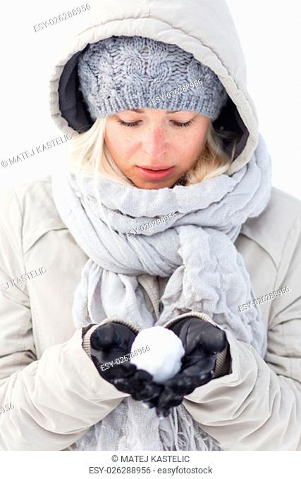 Cute casual young woman wearing glooves, woolen cap and scarf, holding icy snowball in cold winter time. Lady looking down at snowball