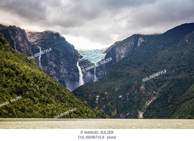 Waterfall flowing from glazier at edge of mountain rock face, Queulat National Park, Chile