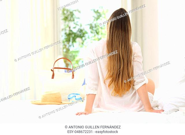 Back view portrait of a woman relaxing sitting on a bed of an hotel room looking through a window in summer vacations