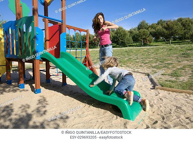 mother surprised by child sliding in green plastic slide. Kid is three years old blonde. Outdoor playground, in public Park Valdebebas, Madrid Spain