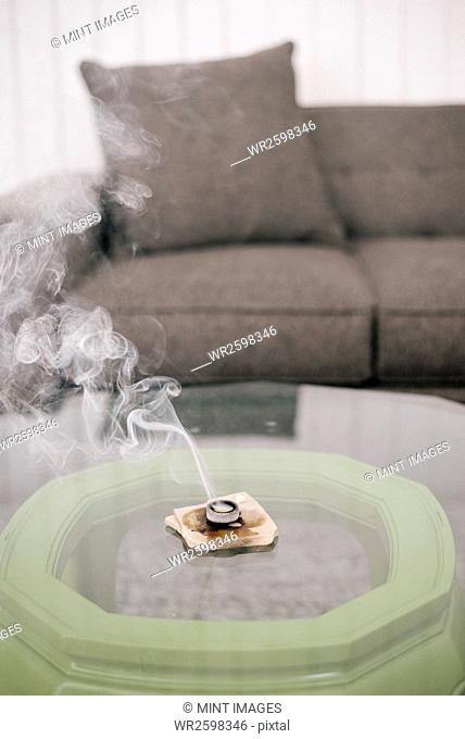 Interior view of a living room, grey sofa and an incense burner on a coffee table