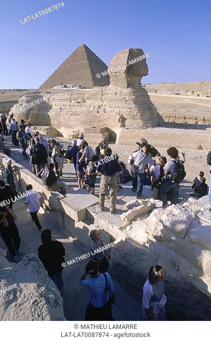 Giza. Sphinx. Part lion part human statue. Profile of head. Cheops Great Pyramid. Crowd of people,tourists