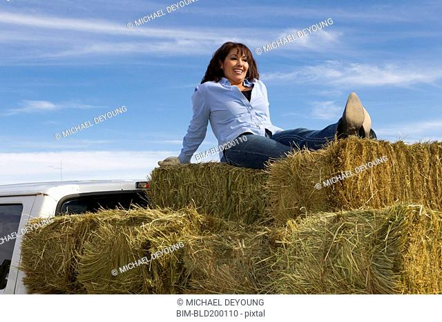 Hispanic woman sitting on hay bales