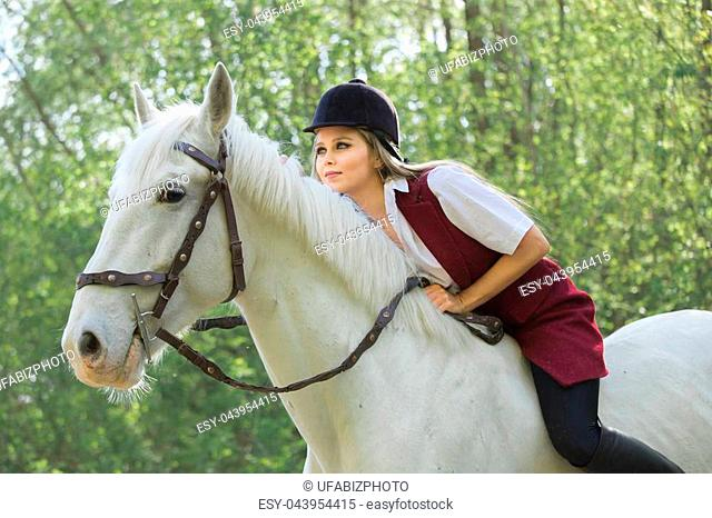 Young jockey girl riding a brown horse in the summer at sunset