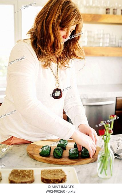 A woman preparing stuffed vine leaves as a lunch dish in a kitchen