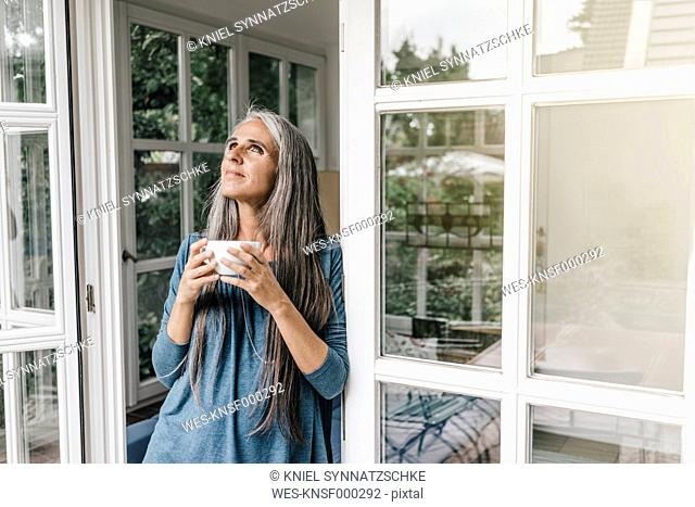 Smiling woman leaning at door frame of her winter garden with cup of coffee looking up