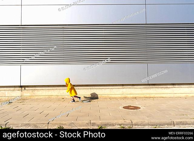 Little girl wearing yellow rain coat running on pavement