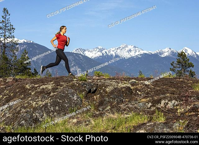 Side view of strong sportswoman running against snowy mountain ridge during fitness workout in countryside