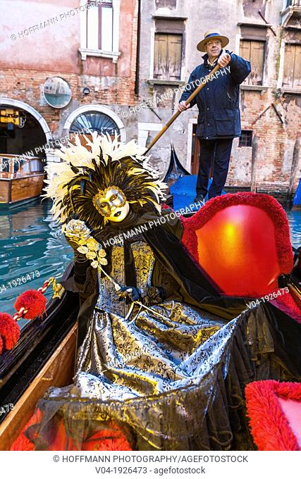 A masked woman in a gondola at the carnival in Venice, Italy, Europe