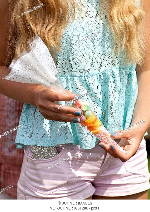 Girl holding candies, close-up