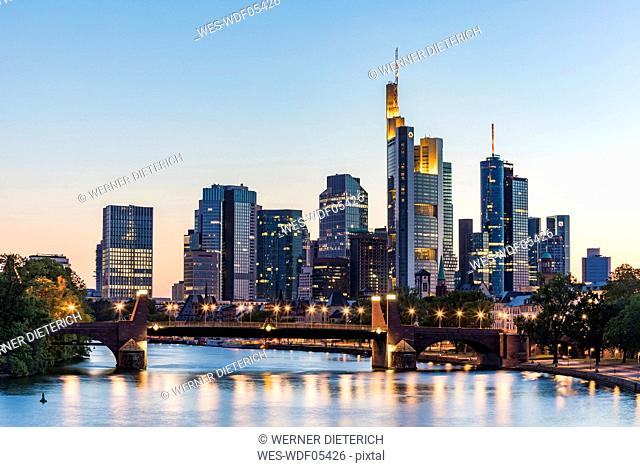 Illuminated bridge over river against clear sky during sunset in Frankfurt, Germany