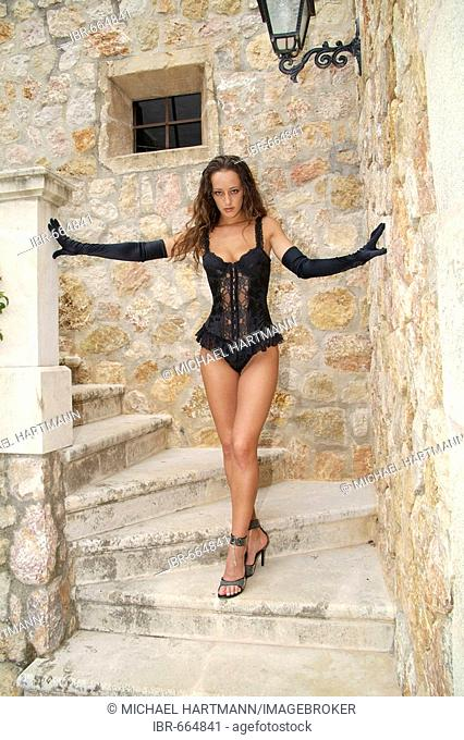 Young woman wearing black lingerie and gloves standing on stone steps at a Finca, traditional Spanish country home in Majorca, Spain