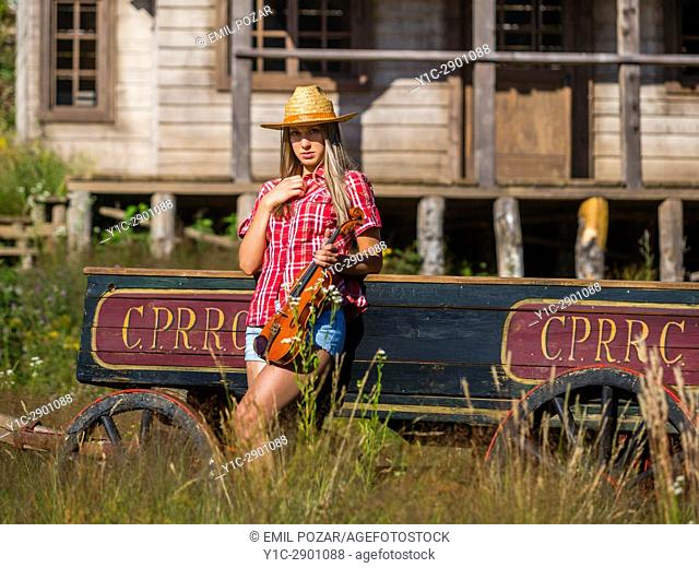 Country-girl with violin inclined on wagon looking at camera in wild west environment. Croatia