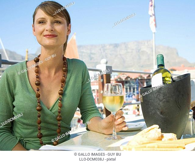 Woman enjoying a glass of wine at the Waterfront with Table Mountain in background, Cape Town, Western Cape Province, South Africa