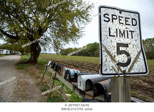 Speed limit sign and mail boxes on country road